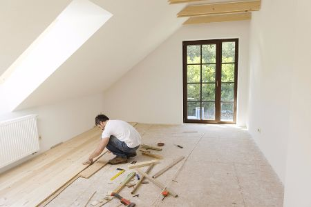 A man in a t-shirt and jeans installing wood floors in a lofted area of a home.
