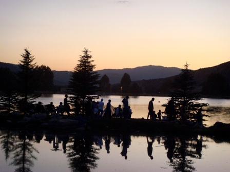 Sunset view of Avon's Nottingham Lake and mountain peaks with a family of tourists in the foreground.